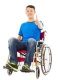 Hombre joven feliz que se incorpora en una silla de ruedas y un pulgar Imagen de archivo