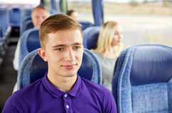 Hombre joven feliz que se sienta en autobús o tren del viaje Imagenes de archivo