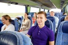 Hombre joven feliz que se sienta en autobús o tren del viaje Foto de archivo libre de regalías