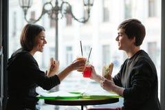 Hombre joven feliz que se sienta en café con el jugo de consumición de la hermana Imagen de archivo libre de regalías