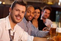 Hombre joven feliz que se sienta en el pub, cerveza de consumición Imagen de archivo libre de regalías