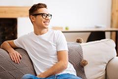 Hombre joven feliz que se sienta en el sofá Imagenes de archivo