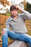 Hombre joven feliz que se sienta en parque del otoño Fotos de archivo