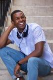Hombre joven feliz que se sienta en pasos con los auriculares Foto de archivo