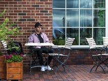 Hombre joven feliz que se sienta en una tabla cerca de una pared Fotografía de archivo libre de regalías