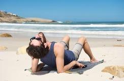 Hombre joven feliz que se sienta solamente en la playa Imagenes de archivo