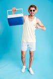 Hombre joven feliz que se sostiene y que señala en un bolso más fresco imagenes de archivo