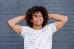 Hombre joven feliz que sonríe con las manos detrás de la cabeza fotos de archivo libres de regalías