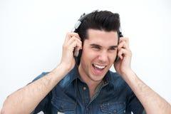 Hombre joven feliz que sonríe con los auriculares fotografía de archivo