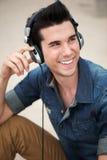 Hombre joven feliz que sonríe con los auriculares imagenes de archivo