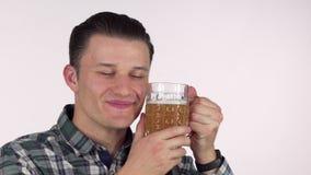 Hombre joven feliz que sonríe con los ojos cerrados, abrazando con una taza de cerveza sabrosa metrajes