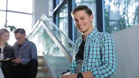 Hombre joven feliz que sonríe en el edificio ligero de la universidad almacen de metraje de vídeo