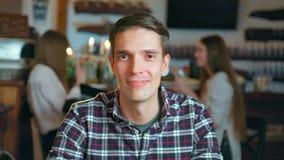Hombre joven feliz que sonríe y que mira in camera en restaurante almacen de video