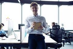 Hombre joven feliz que sonr?e en la c?mara con una tableta en su mano imagen de archivo