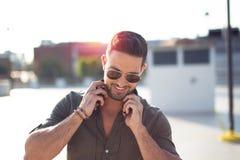 Hombre joven feliz que sostiene el retrato al aire libre de los auriculares foto de archivo