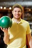 Hombre joven feliz que sostiene la bola en club de los bolos Imagen de archivo libre de regalías