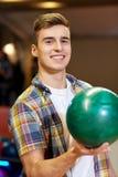 Hombre joven feliz que sostiene la bola en club de los bolos Imágenes de archivo libres de regalías