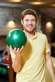 Hombre joven feliz que sostiene la bola en club de los bolos Imagenes de archivo