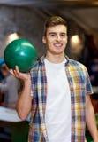 Hombre joven feliz que sostiene la bola en club de los bolos Fotos de archivo libres de regalías