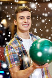 Hombre joven feliz que sostiene la bola en club de los bolos Foto de archivo libre de regalías