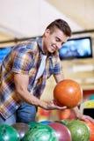 Hombre joven feliz que sostiene la bola en club de los bolos Foto de archivo