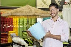 Hombre joven feliz que sostiene un recuerdo en tienda Imagenes de archivo