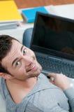Hombre joven feliz que trabaja en la computadora portátil Fotos de archivo