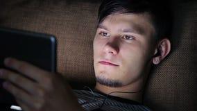Hombre joven feliz que usa el ordenador de Ipad de la tableta de Digitaces metrajes