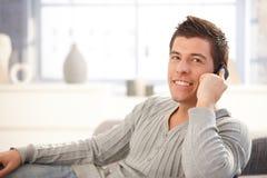 Hombre joven feliz que usa el teléfono móvil Foto de archivo libre de regalías