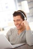 Hombre joven feliz que usa la computadora portátil y el receptor de cabeza Imagen de archivo libre de regalías
