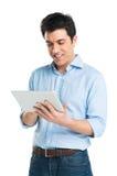 Hombre joven feliz que usa la tableta de Digitaces Imagen de archivo