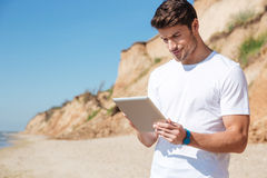 Hombre joven feliz que usa la tableta en la playa fotos de archivo