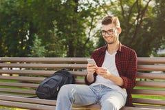 Hombre joven feliz que usa smartphone al aire libre Fotografía de archivo libre de regalías