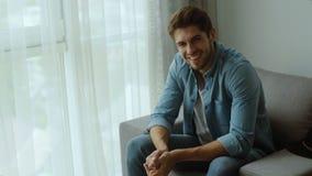 Hombre joven feliz Retrato del hombre joven hermoso en la camisa sport que mantiene los brazos cruzados y que sonríe en casa metrajes
