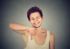 Hombre joven feliz sarcástico que muestra gesto de mano de los pulgares abajo Imagen de archivo libre de regalías