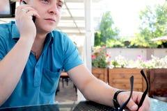 Hombre joven feliz satisfecho con la buena conexión móvil en la itinerancia mientras que habla con los amigos en el dispositivo d imagenes de archivo