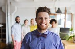 Hombre joven feliz sobre el equipo creativo en oficina Imágenes de archivo libres de regalías