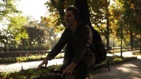 Hombre joven feliz, sonriente en la ropa casual negra, auriculares que montan una bici por el parque pavimentado de la ciudad con almacen de metraje de vídeo