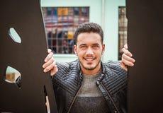 Hombre joven feliz, sonriente entre las puertas del metal imágenes de archivo libres de regalías
