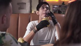 Hombre joven flaco lindo en vidrios y guantes negros que come shawarma sabroso El hombre que goza de los alimentos de preparación metrajes