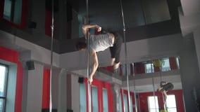 Hombre joven flexible que ejercita elementos de la danza del polo en un polo almacen de video