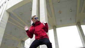 Hombre joven fresco que lleva la chaqueta roja y las gafas de sol que golpean emocionalmente metrajes