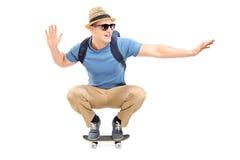 Hombre joven fresco que monta un pequeño monopatín Imágenes de archivo libres de regalías