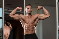 Hombre joven Front Double Biceps Pose de ejecución Fotos de archivo libres de regalías