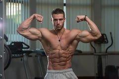 Hombre joven Front Double Biceps Pose de ejecución Fotografía de archivo