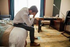 Hombre joven frustrado en el traje formal que se sienta en cama además del bolso del equipaje Hombre de negocios que piensa en pr imágenes de archivo libres de regalías