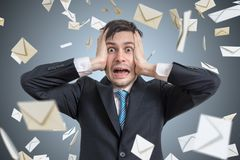 Hombre joven frustrado y muchos sobres que caen Muchos email y concepto del Spam foto de archivo libre de regalías