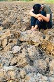 Hombre joven frustrado y triste que se sienta en tierra estéril Fotografía de archivo libre de regalías