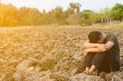 Hombre joven frustrado y triste que se sienta en tierra estéril Con el sol Foto de archivo libre de regalías