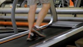 Hombre joven fuerte en la rueda de ardilla en gimnasio almacen de metraje de vídeo